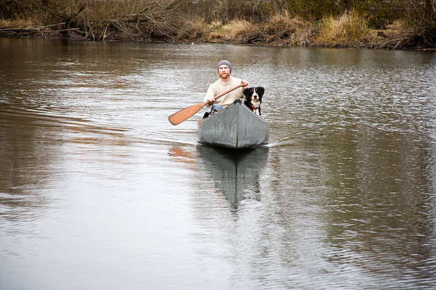 Young Man Canoeing With His Dog